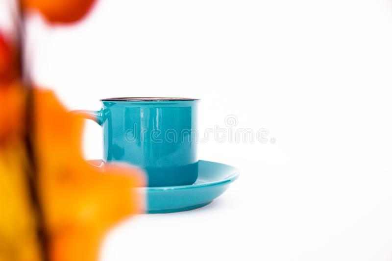 Blue Cup on saucer on white background through yellow autumn maple leaf closeup, copy space, flat lay stock images