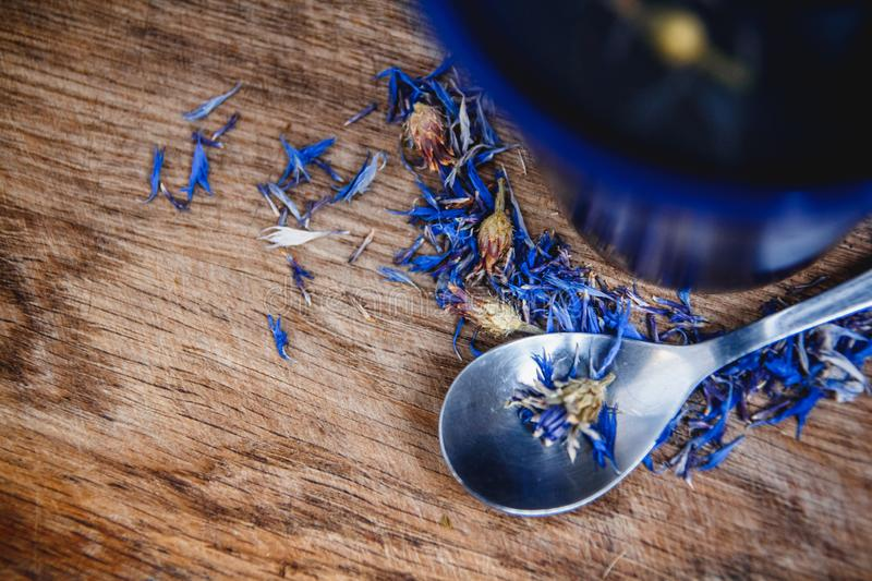 Blue cup and spoon with flowered black tea on a wooden background. Breakfast, health, herbal therapy, healthy food royalty free stock images
