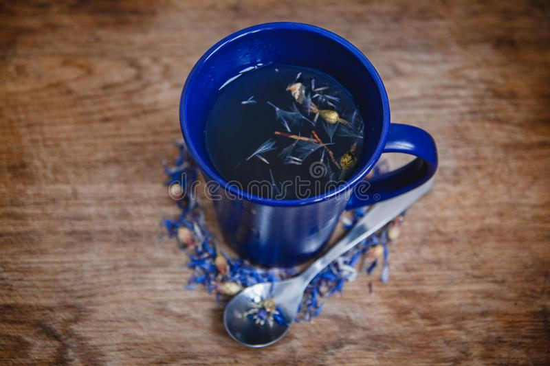 Blue cup and spoon with flowered black tea on a wooden background. Breakfast, health, herbal therapy, healthy food stock photography