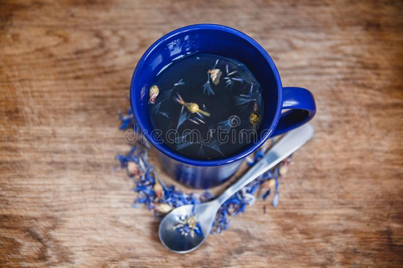 Blue cup and spoon with flowered black tea on a wooden background. Breakfast, health, herbal therapy, healthy food stock photo