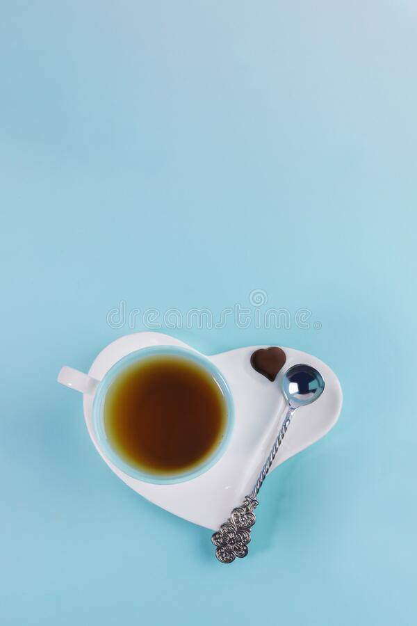 Blue cup of tea with silver spoon and one chocolate candy on white saucer in heart shape on light blue background. royalty free stock image