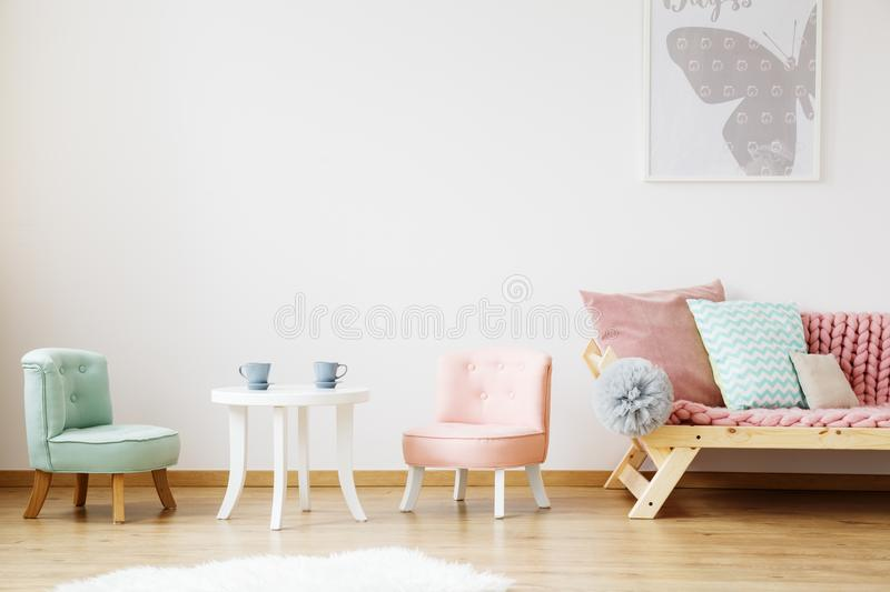 Blue cups on white children`s table. And chairs in scandinavian style kids room royalty free stock photo