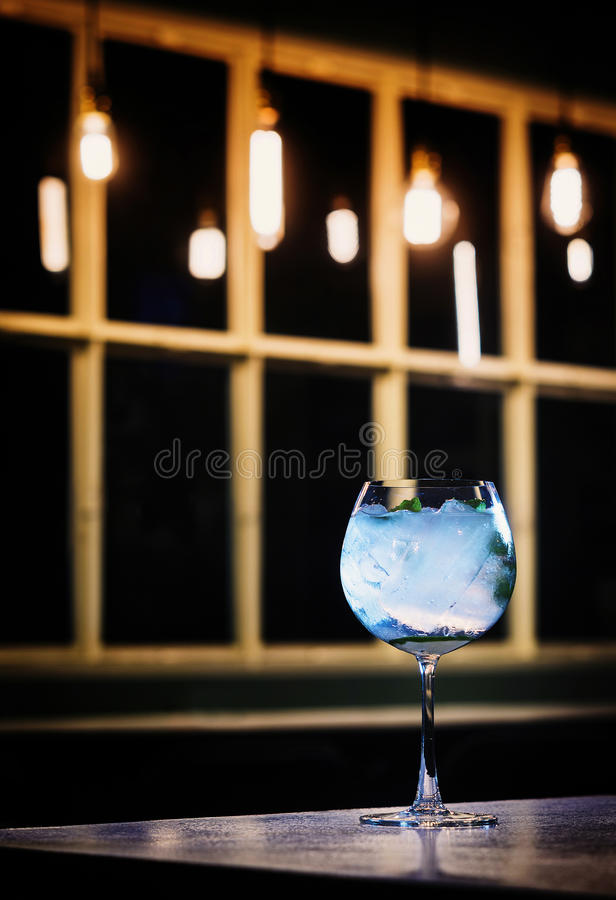 Blue curacao and vodka cocktail drink in trendy bar. At night royalty free stock images