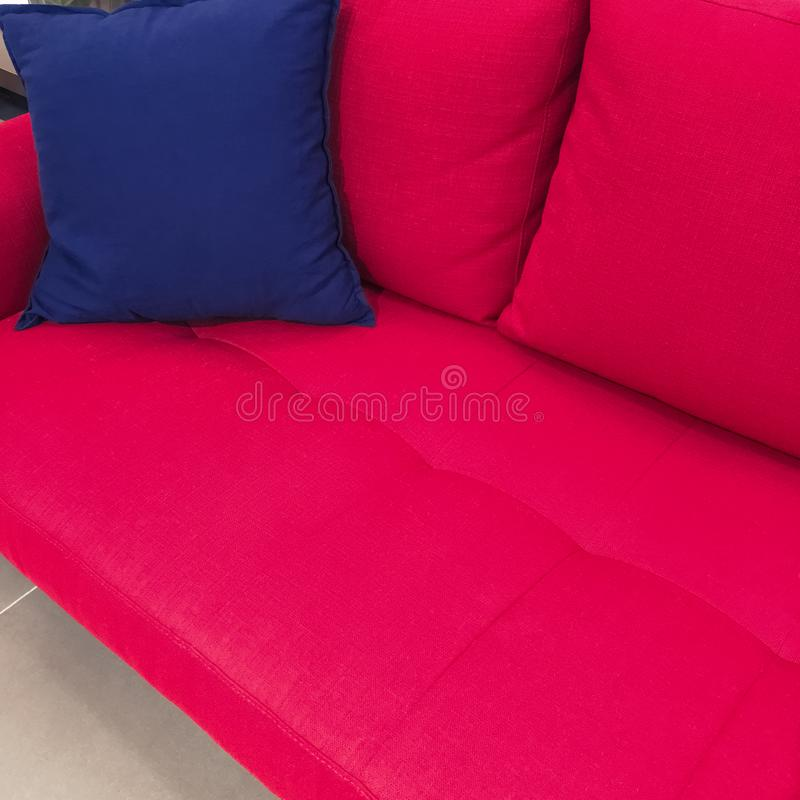 Blue cushion on a red sofa. Blue cushion on a bright red textile sofa. Modern furniture stock image