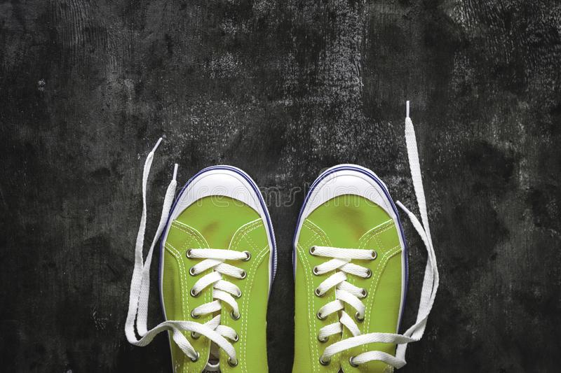 blue-cyan-green-turquoise sneakers with untied laces on a dark concrete background. Copy space. View from above royalty free stock photography