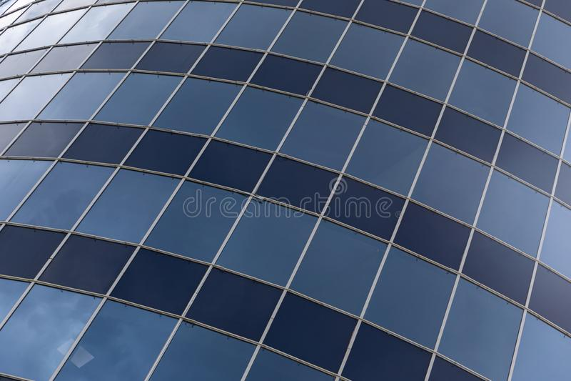 Blue and dark blue glass square and rectangular windows on building facade royalty free stock image