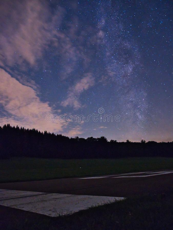 Blue dark night sky with many stars above field of trees. Milkyway cosmos background royalty free stock photo