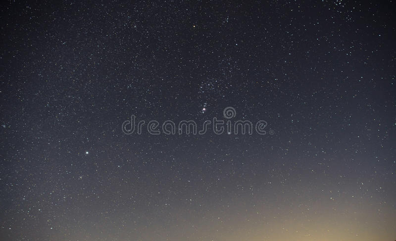 Blue dark night sky with many stars above field of trees. Milkyway cosmos background stock photo