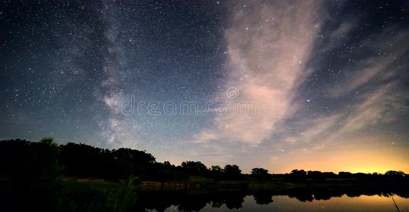 Blue dark night sky with many stars above field of trees. Yellowstone park. Milkyway cosmos background stock photo