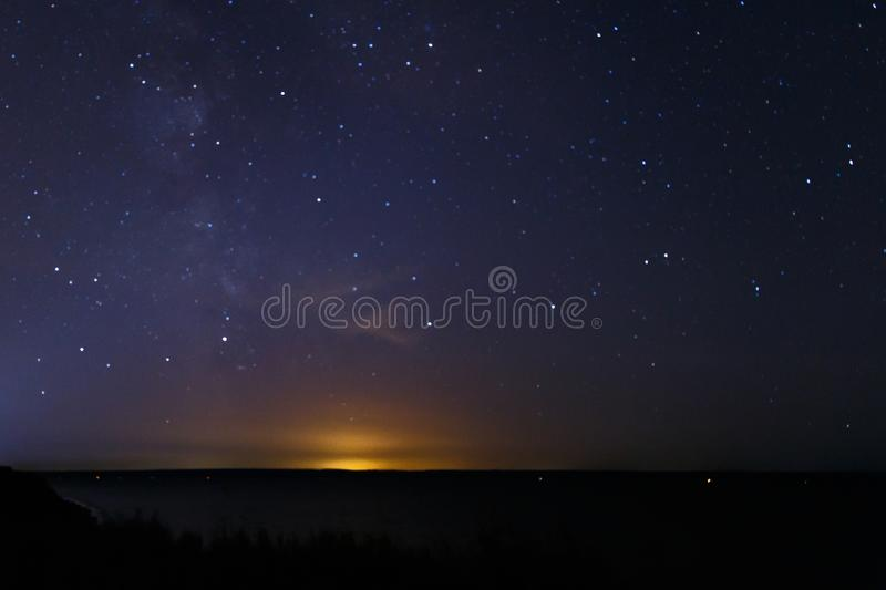 Blue dark night sky with many stars. Milky way cosmos background. The stars in the night sky. Starry blue night sky royalty free stock photography