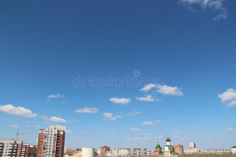 Blue day sky with white clouds and sunlight. A city landscape background. royalty free stock image