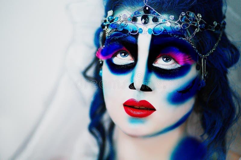 Blue dead bride. Beautiful woman dead bride. Jewelry white long veil, red lips. Creative dark makeup, conceptual idea for Halloween. Eerie nightmare darkness stock images