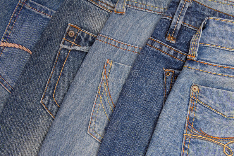 Blue denim background, pile of jeans, back side royalty free stock photo