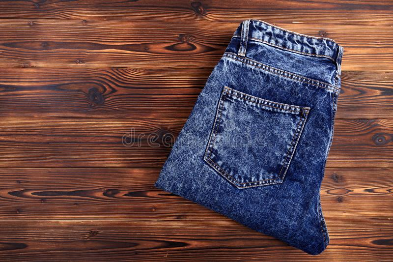 Blue denim jeans  on wooden background. Image royalty free stock photos