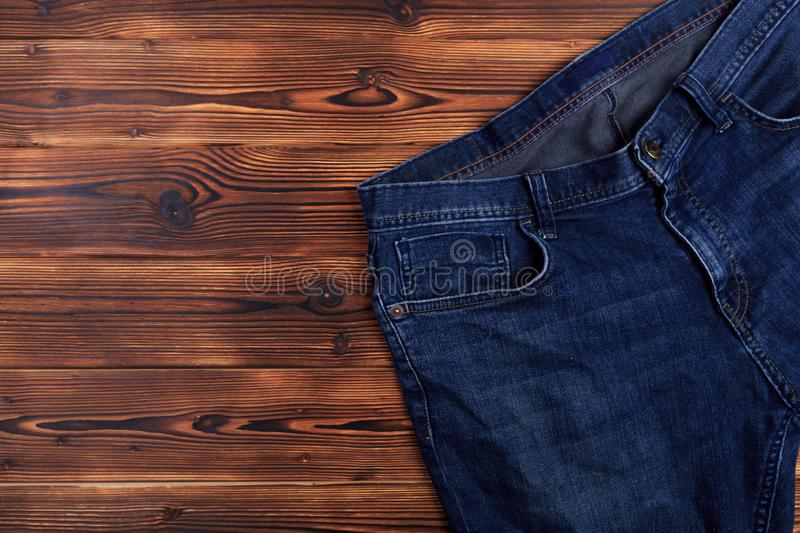 Blue denim jeans  on wooden background. Image stock photos
