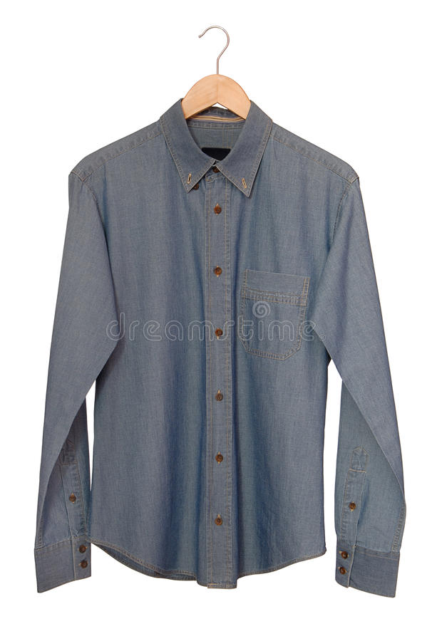 A blue denim shirt is on clothes-hanger. royalty free stock photos
