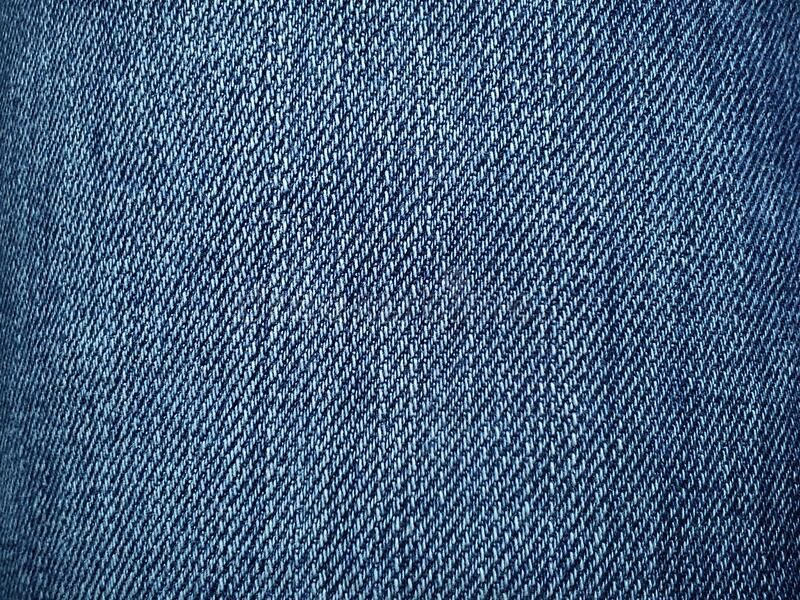 Blue denim. Texture of cotton coarse material. A fragment of a natural rag indigo. Vertical furrows, dark and light threads,. Individual stitches are noticeable royalty free stock image