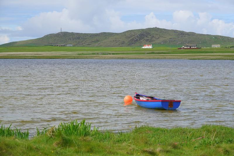 Blue dinghy moored to buoy in lake. A small blue dinghy moored to orange buoy in Loch Bhasapoll on the island of Tiree in Scotland royalty free stock image