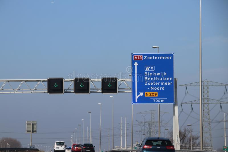 Blue direction sign on motorway A12 heading to Den Haag and Zoetermeer in the Netherlands stock image