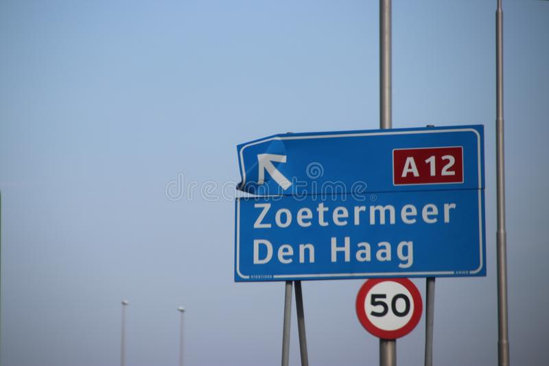 Blue direction sign on motorway A12 heading to Den Haag and Zoetermeer in the Netherlands stock photography