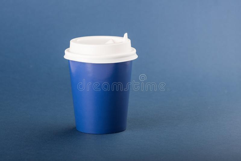 Blue disposable cup with white cap on a blue background.  stock photography