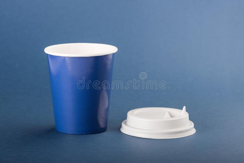 Blue disposable cup with white cap on a blue background.  royalty free stock images