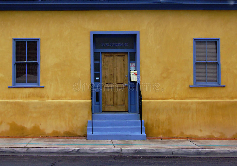 Blue Door in Barrio. Bright yellow building with blue doors and windows is found in what was once the Barrio royalty free stock photo