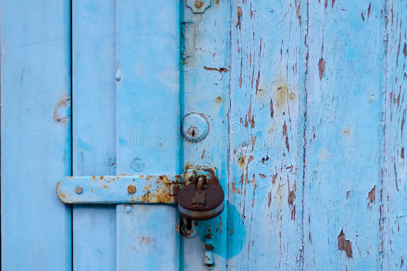 Blue door. With cracked paint and rusty lock royalty free stock photography