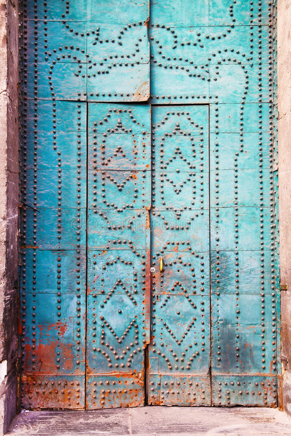 Blue door with decorative elements. Ancient wooden blue door with decorative elements and rivets stock image
