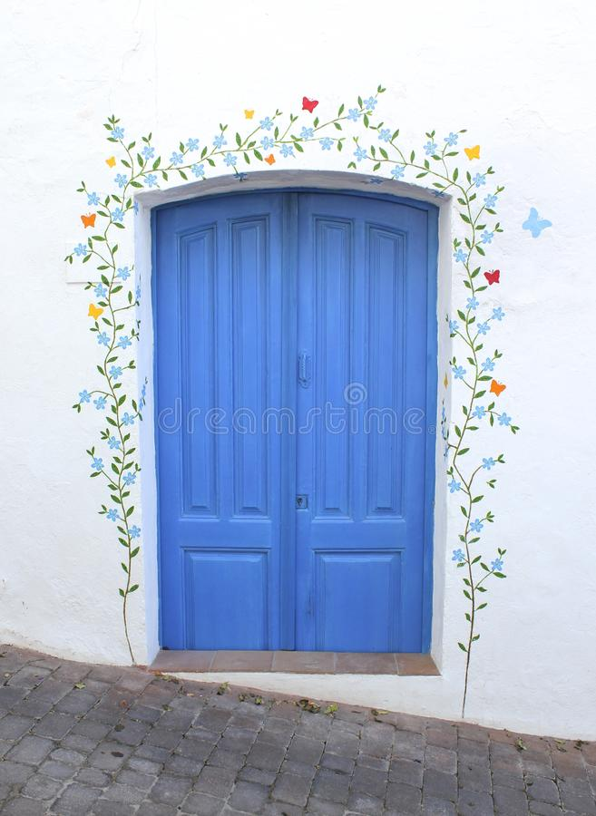 A blue door with a flower mural on the white washed wall royalty free stock image