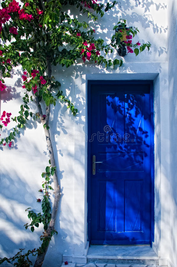 Blue door in greece. With plant climbing on the wall stock photos