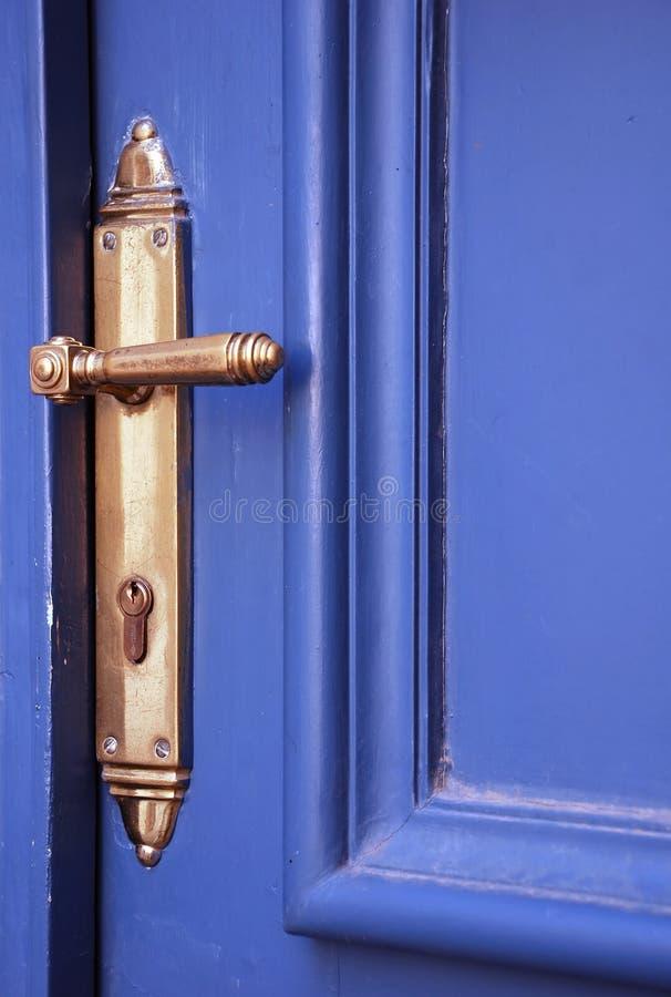 Blue door with handle. Detail of blue door with old handle royalty free stock photo
