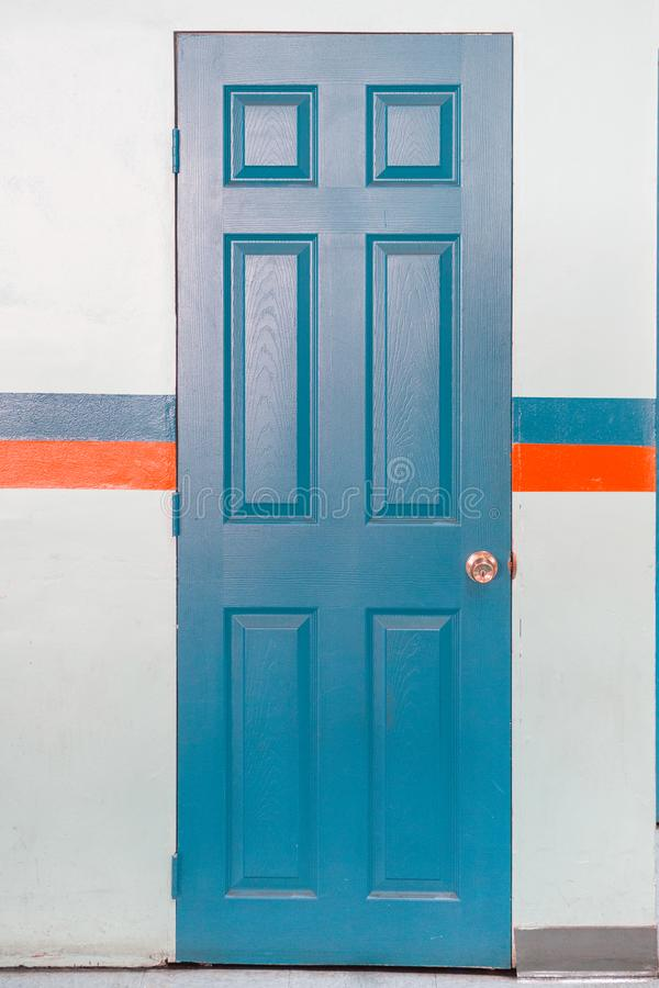 Blue Door with handle lock. With blue and orange striped stock image