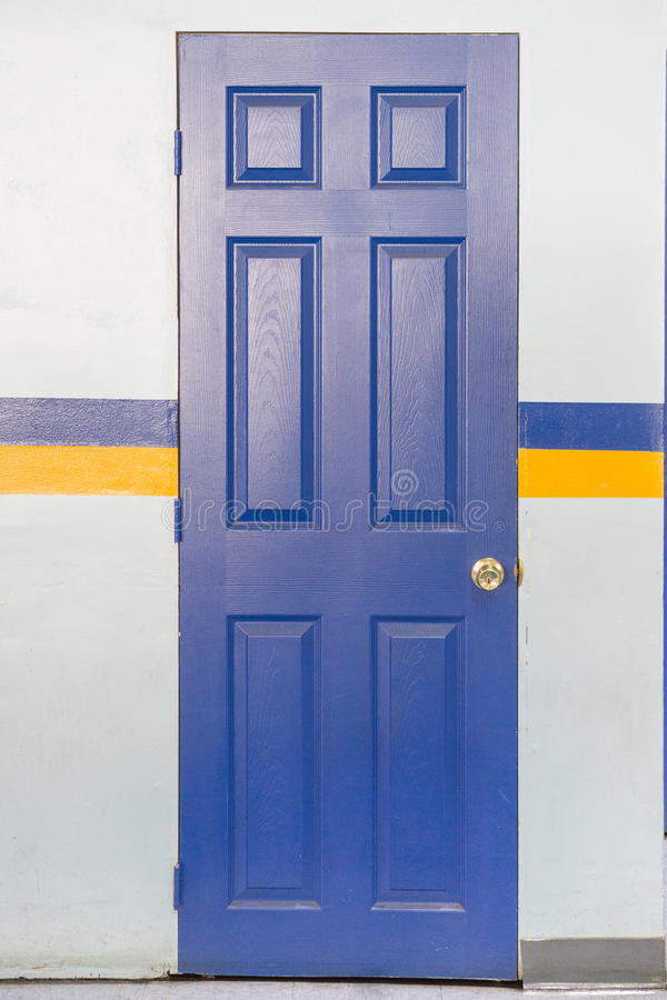 Blue Door with handle lock. With blue and yellow striped royalty free stock image