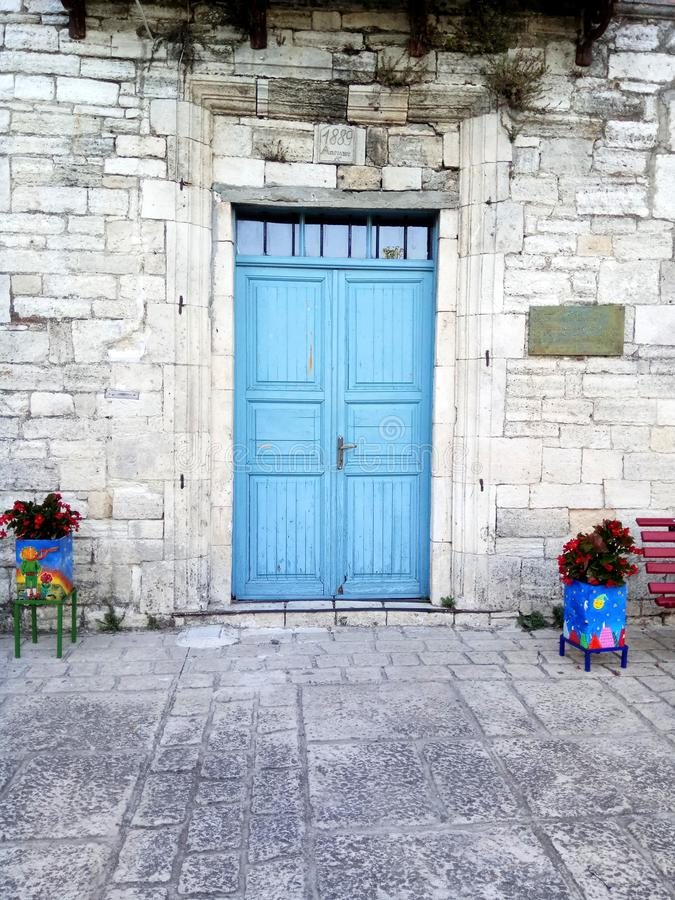 Blue door in old museum at Afytos, Kassanra, Chalkidiki. Flowers in pots in the center of the traditional village. royalty free stock images