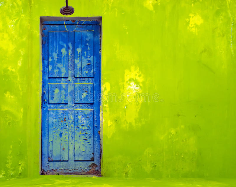 Blue Door in Shabby Green Wall royalty free stock image