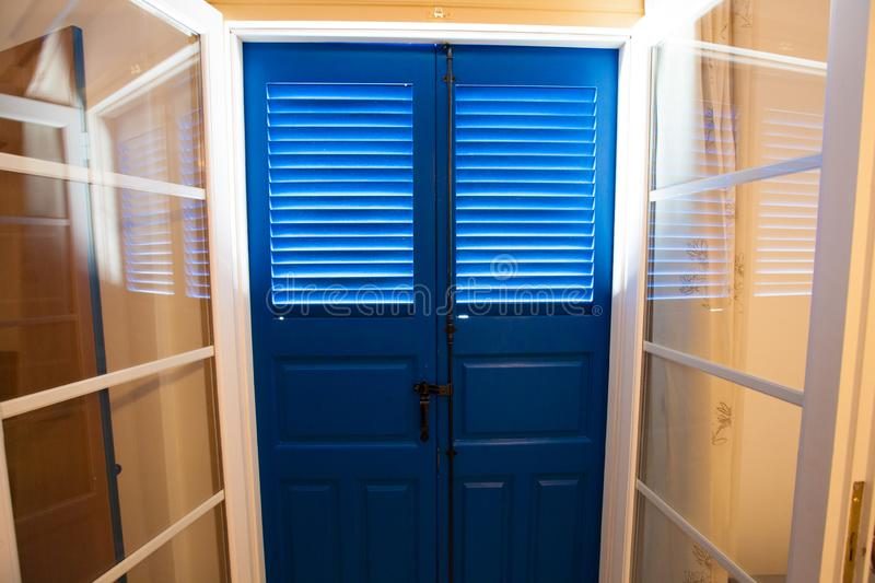 Blue door and window with shutters royalty free stock photography