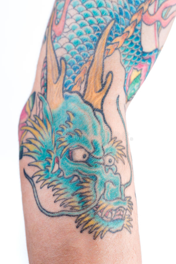 Blue Dragon Tattoo on Arm. A detailed shot of a blue/green dragon tattoo in Japanese style on the forearm, elbow and bicep of a white male isolated on a white stock photography