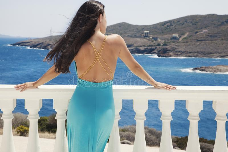 Blue dress and blue sea. Beautiful woman in a blue backless dress stands next to the white pillars and looking at the sea royalty free stock photography