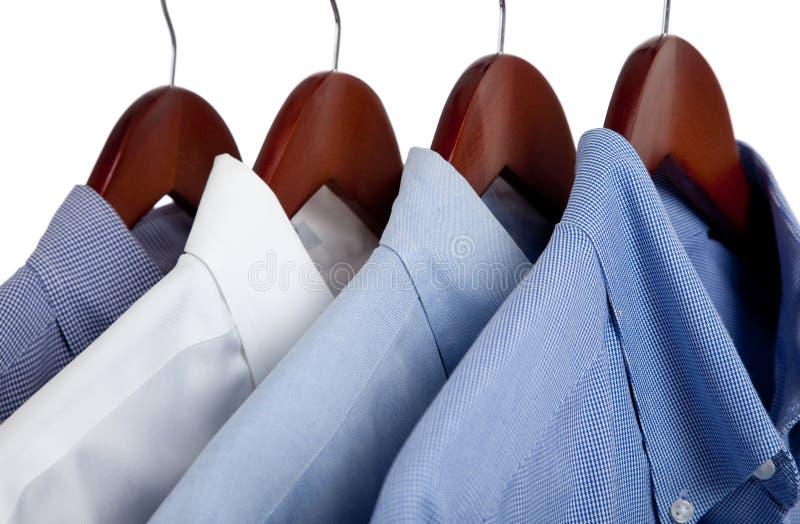 Blue dress shirts on wooden hangers stock photos