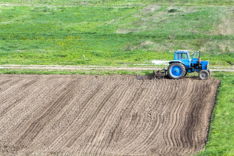 Blue dusty tractor with seedbed cultivator standing at the edge. Of freshly plowed and cultivated field, soil prepared for sowing. Agriculture, farming and royalty free stock photos