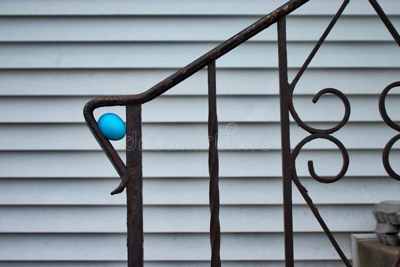 Blue dyed Easter egg, hidden for an egg hunt, in crook of fence railing on concrete stairs of midwestern home. Blue dyed Easter egg, hidden for an egg hunt, in royalty free stock image
