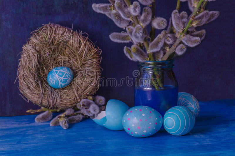 Blue Easter egg in the nest and branch of a willow stock photos