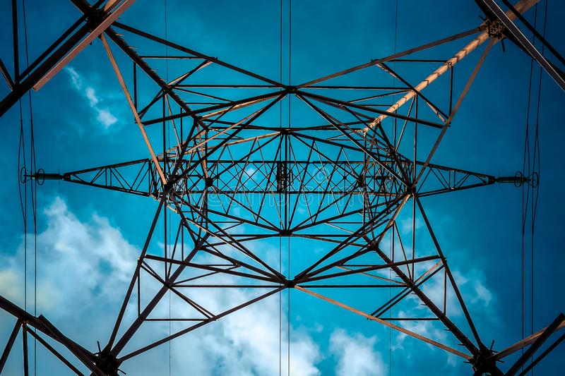 Blue Electric Lines and sky. High voltage line pylon seen from below with blue sky