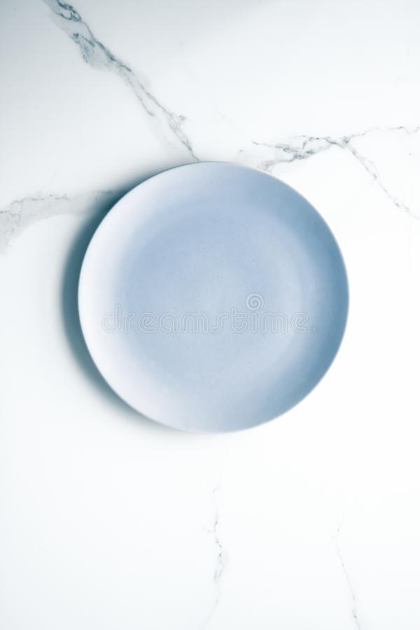 Serve the perfect plate. Blue empty plate on marble, flatlay - stylish tableware, table decor and food menu concept. Serve the perfect dish royalty free stock photos