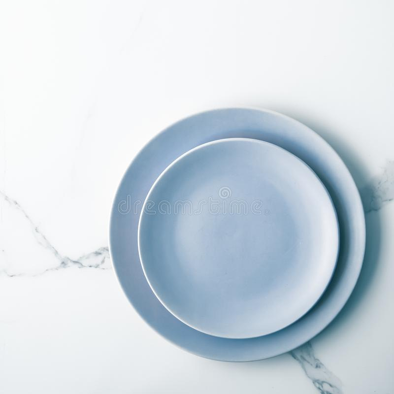 Serve the perfect plate. Blue empty plate on marble, flatlay - stylish tableware, table decor and food menu concept. Serve the perfect dish royalty free stock photography