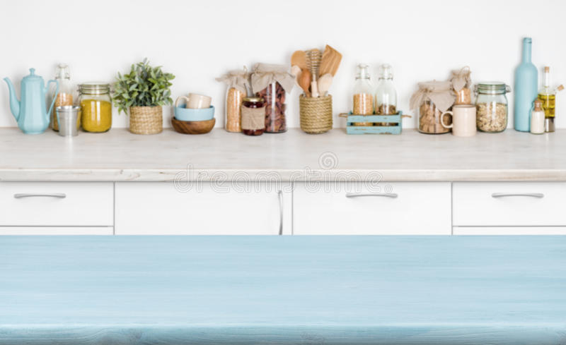 Blue empty wooden kitchen table over blurred food ingredients background.  stock photography