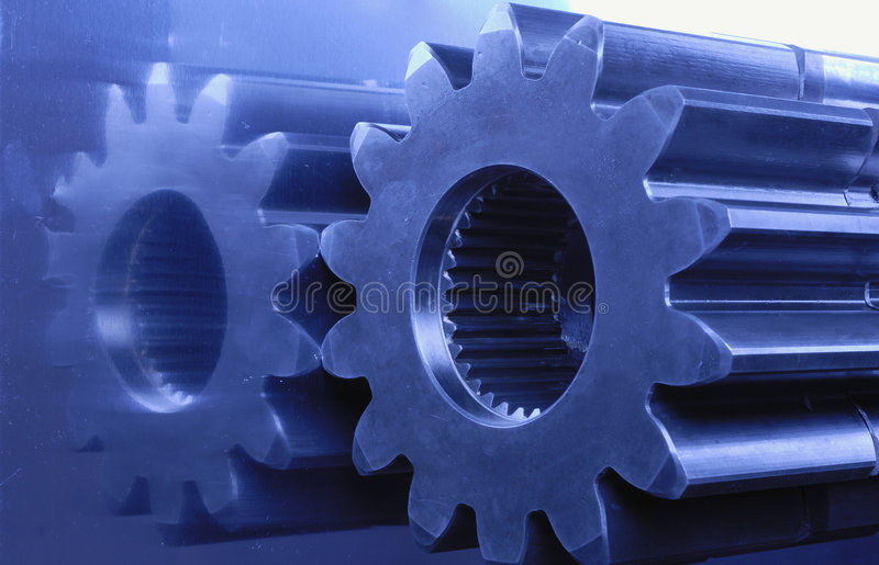 Blue engineering. Gears, cogs connecting with bearings against titanium in blue stock images