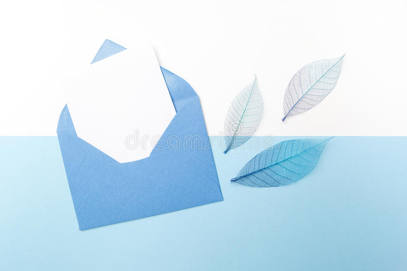 Blue envelope with blank paper sheet included. Top view. Flat lay. stock image