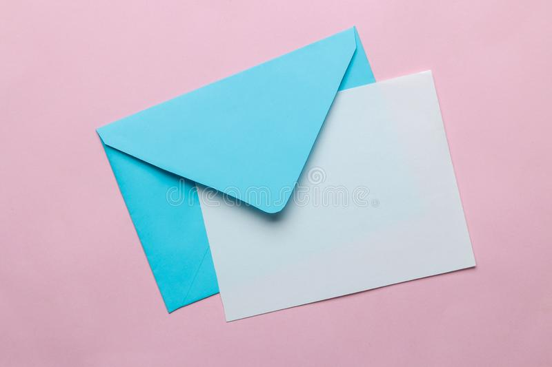 Blue envelope with a blank for text on a bright trendy pink background. top view royalty free stock photo